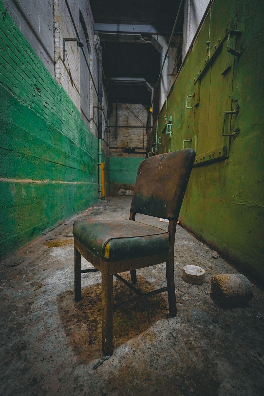 brown wooden armchair beside green wall