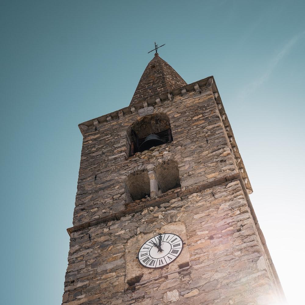 brown brick tower with analog clock