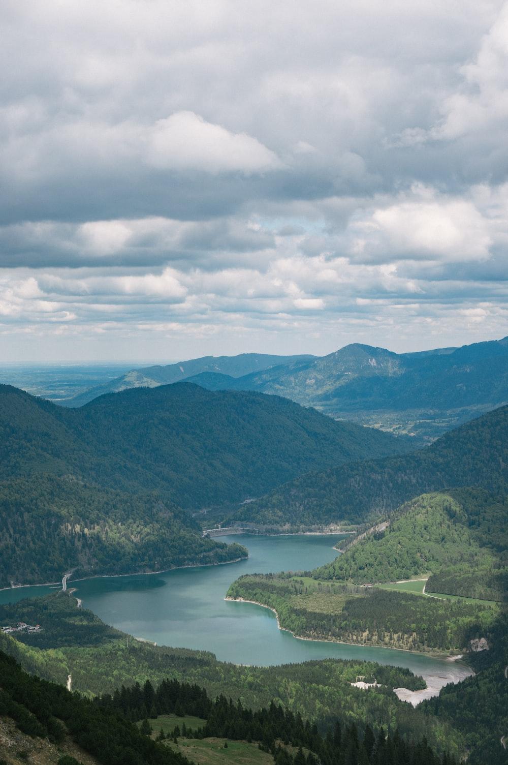 green mountains near lake under white clouds during daytime