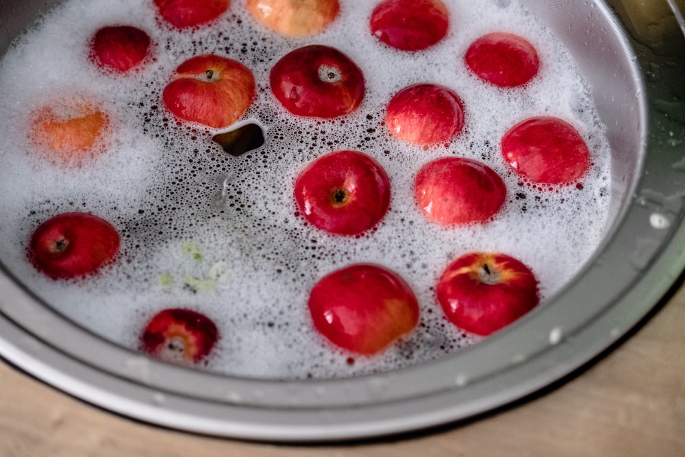 red and brown round fruit on clear glass plate