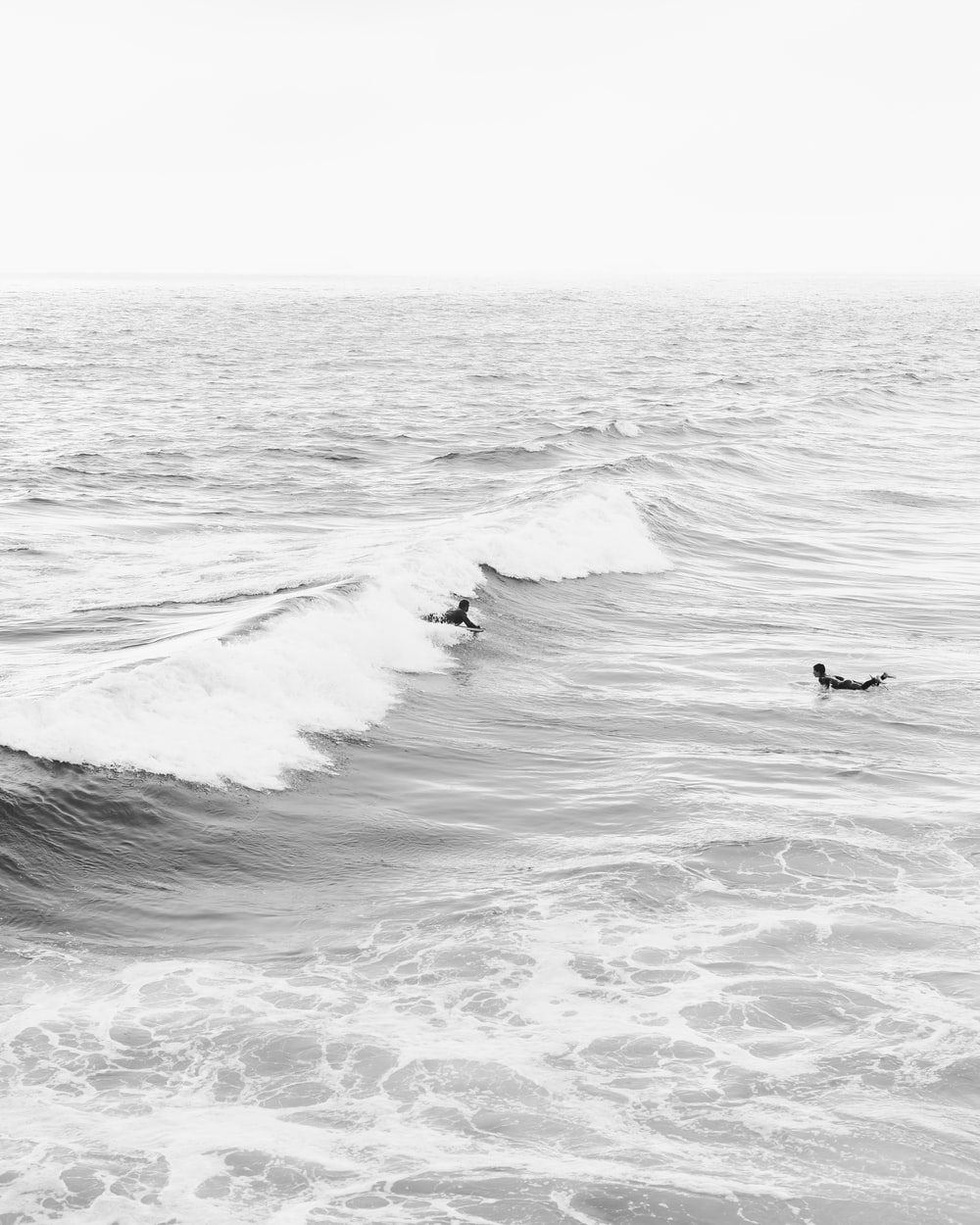 grayscale photo of person surfing on sea waves
