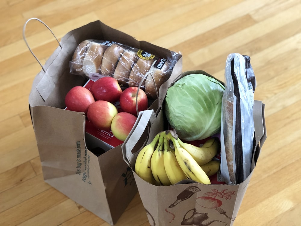 apples and bananas in brown cardboard box