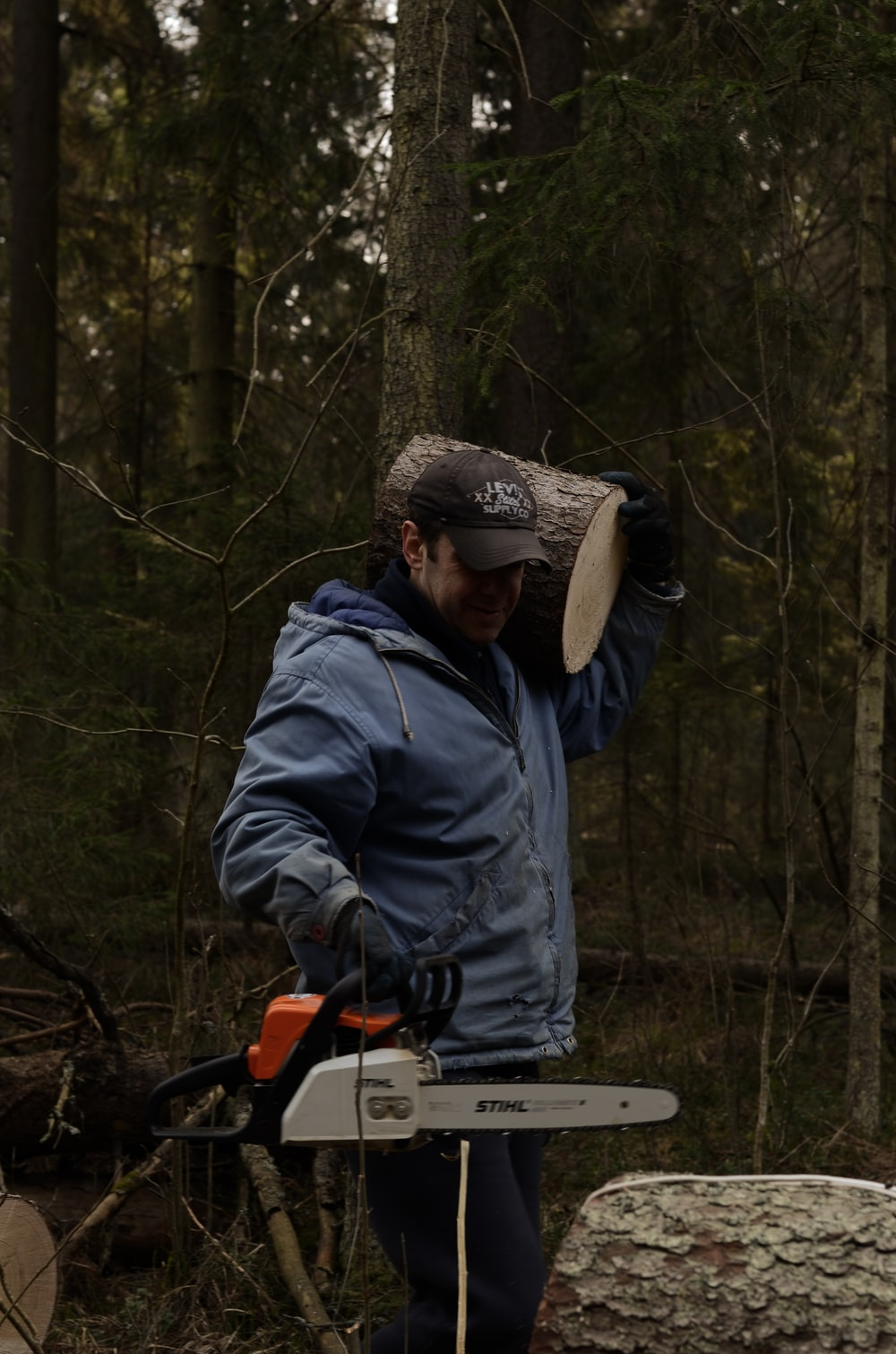 man in blue jacket and brown knit cap holding orange and black power tool