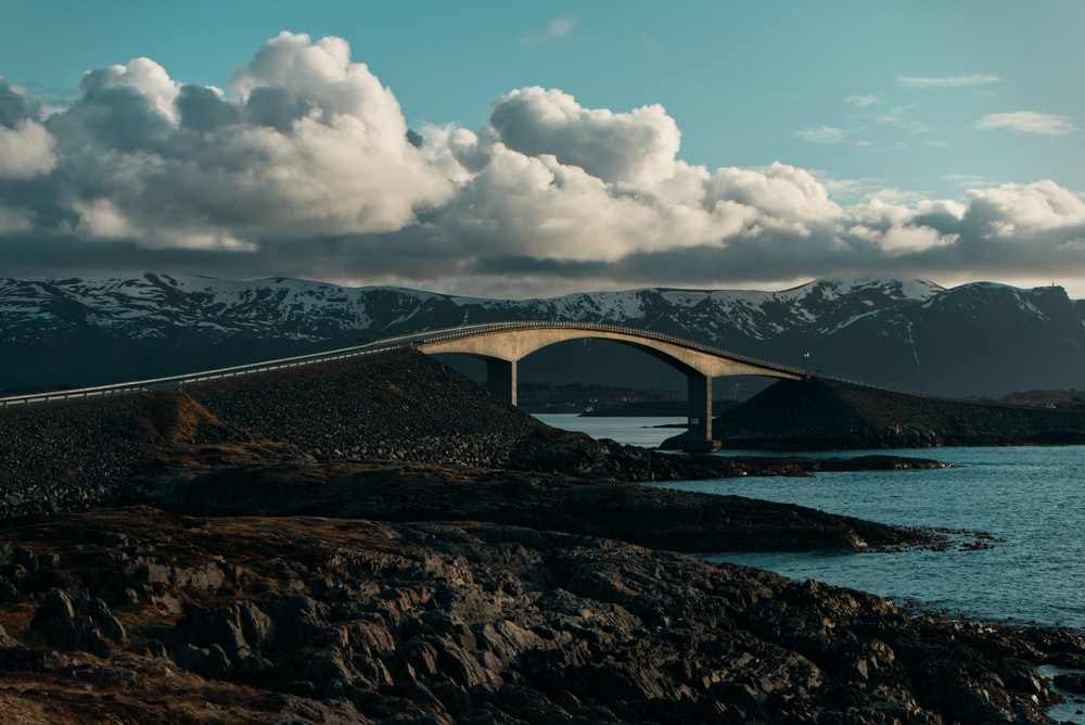brown bridge over blue sea under white clouds and blue sky during daytime