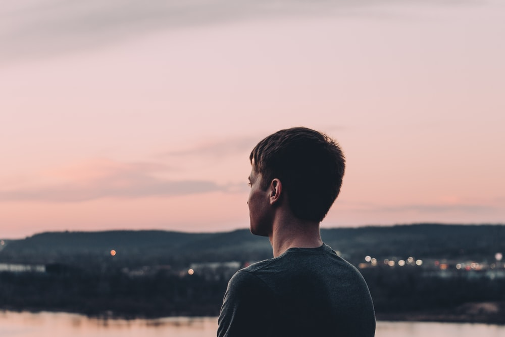 man in black shirt standing near body of water during sunset