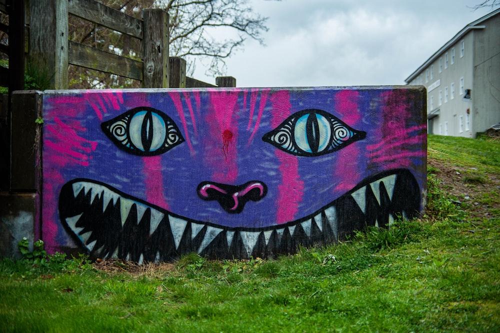 purple and black graffiti on wall