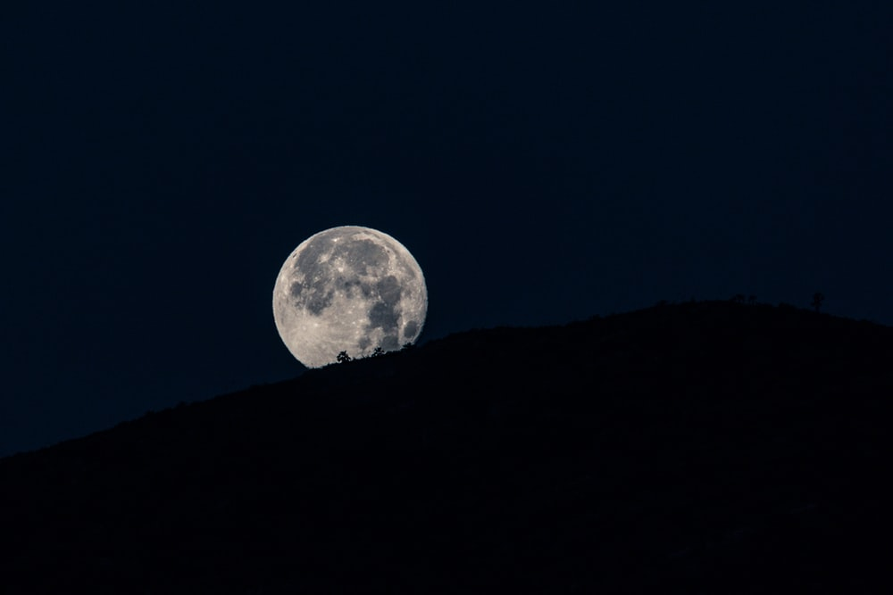 silhouette of mountain under full moon