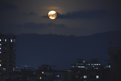 Thāne full moon over city buildings during night time