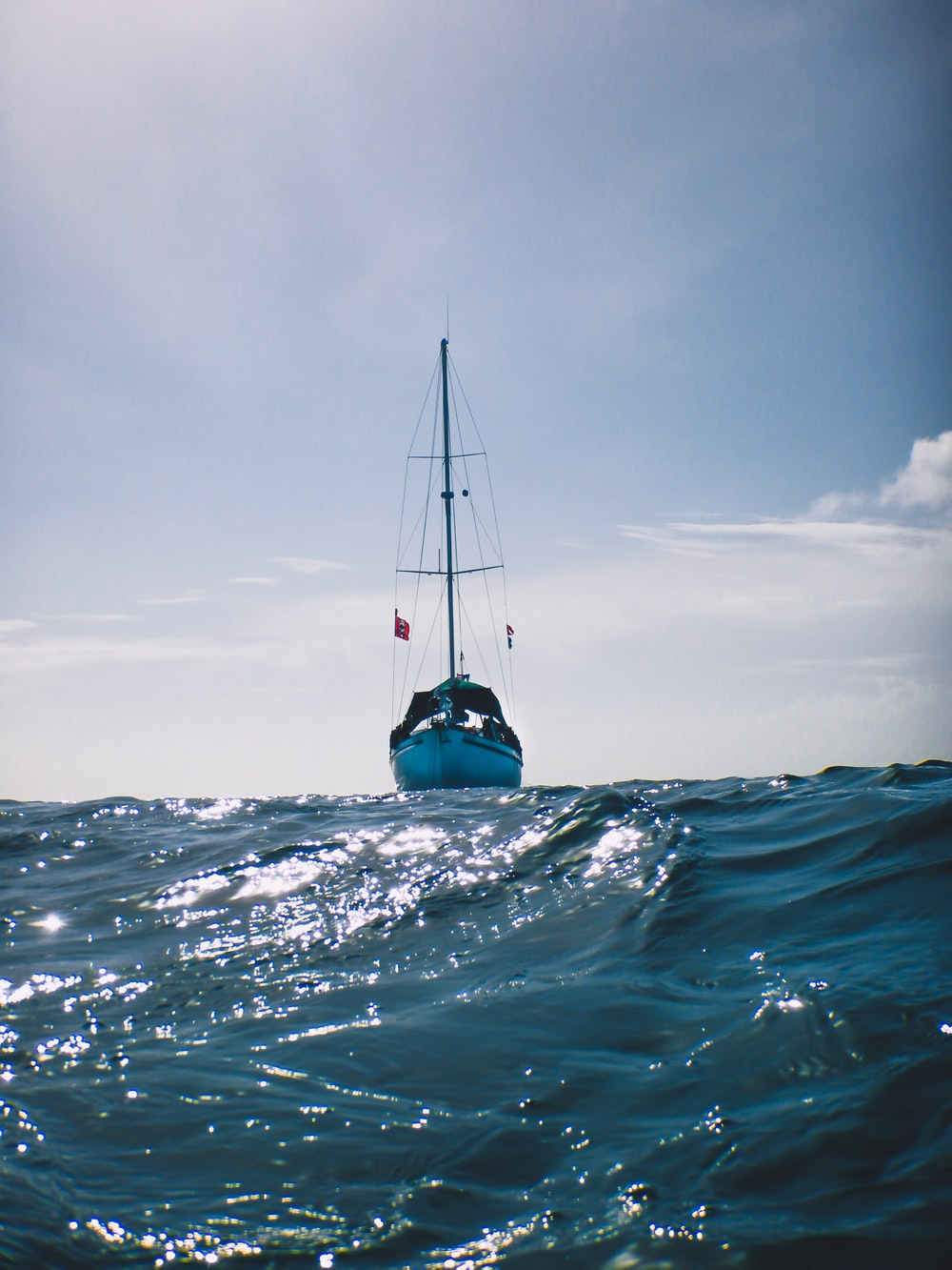 blue and white sail boat on body of water