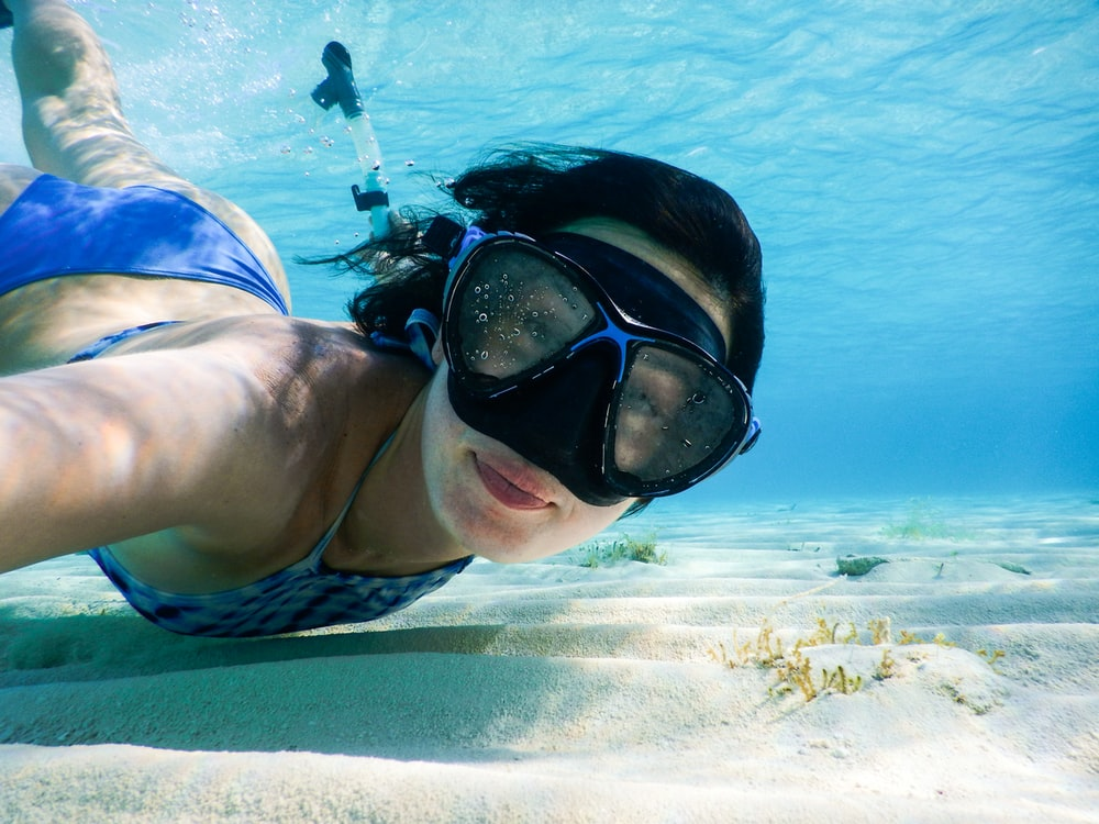 woman in blue swimming goggles and swimming goggles in water