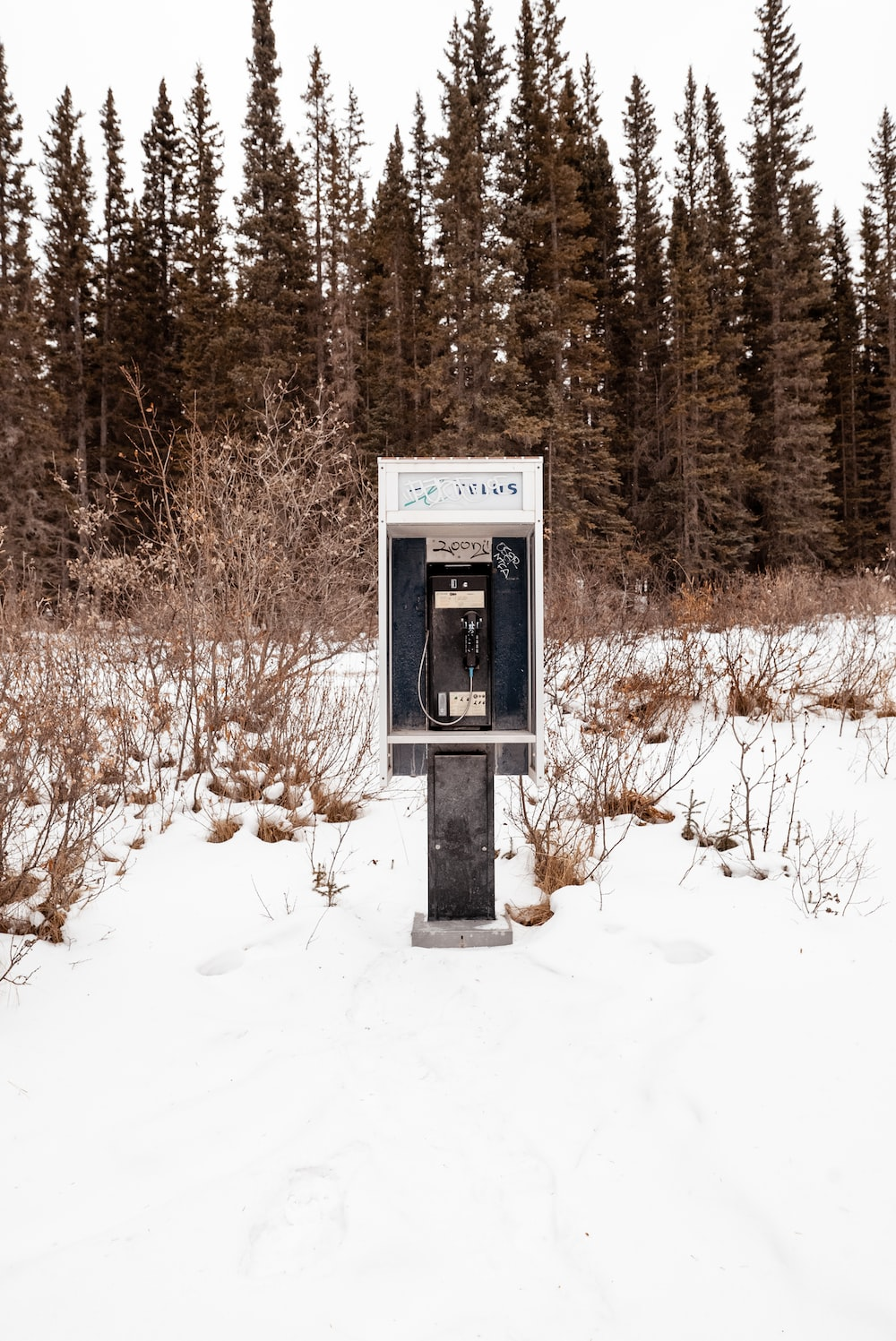 black and gray telephone booth on snow covered ground