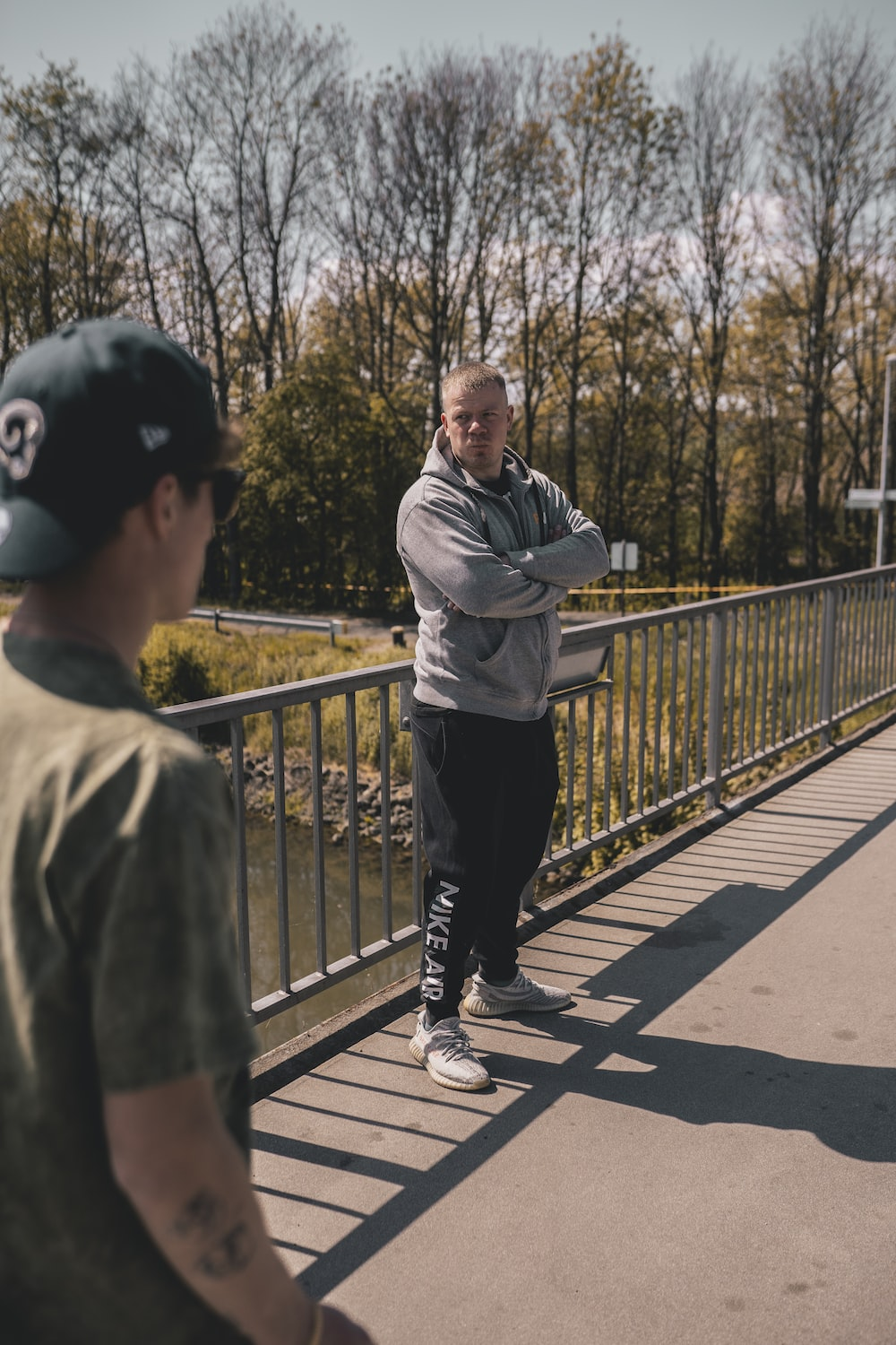man in gray jacket and black pants standing on bridge during daytime