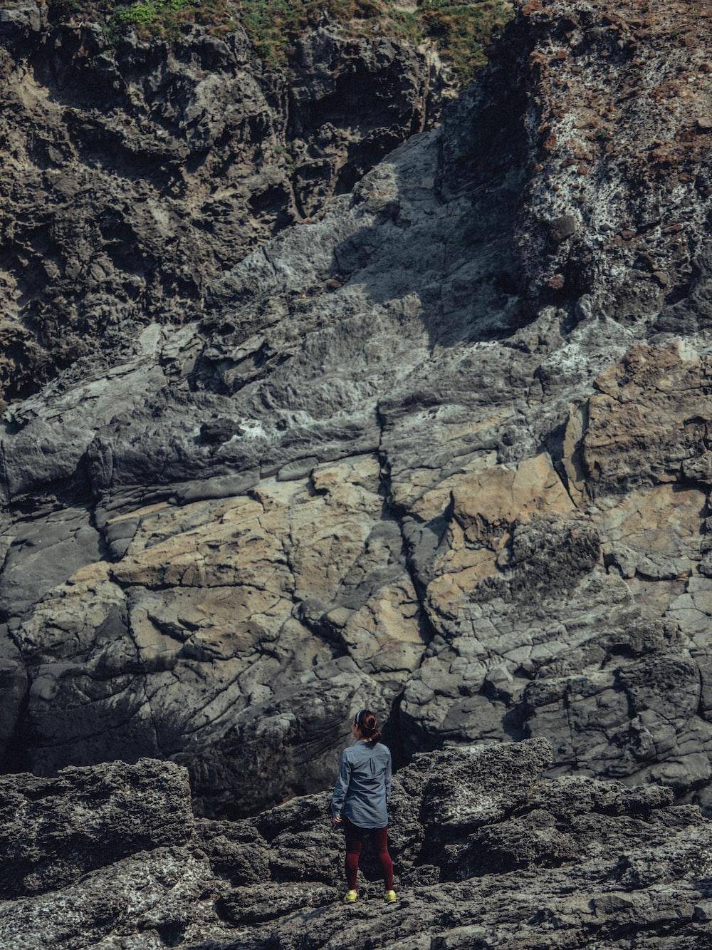 man in blue denim jacket standing on rocky mountain during daytime
