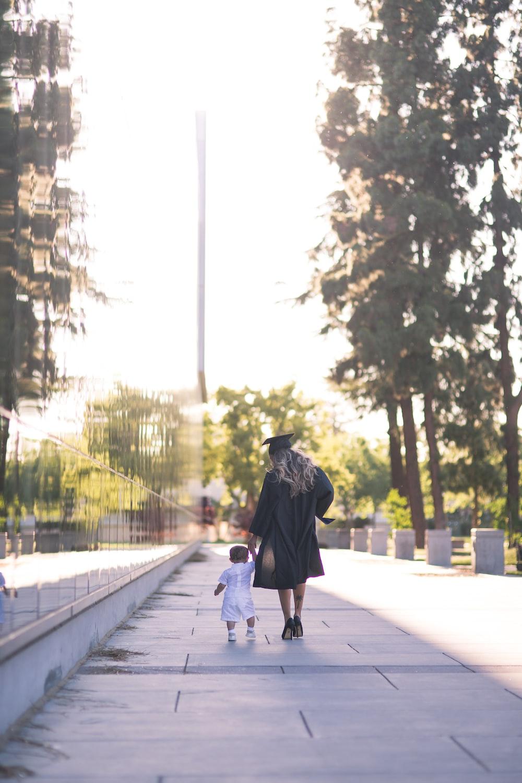 person in black hoodie walking on sidewalk during daytime