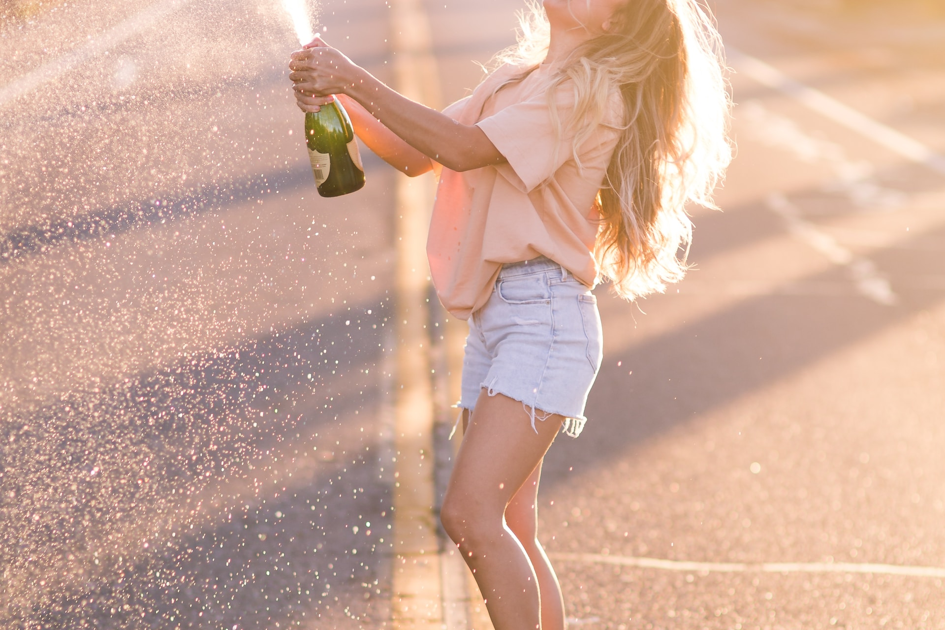 woman in white shirt and blue denim shorts holding green bottle standing on road during daytime