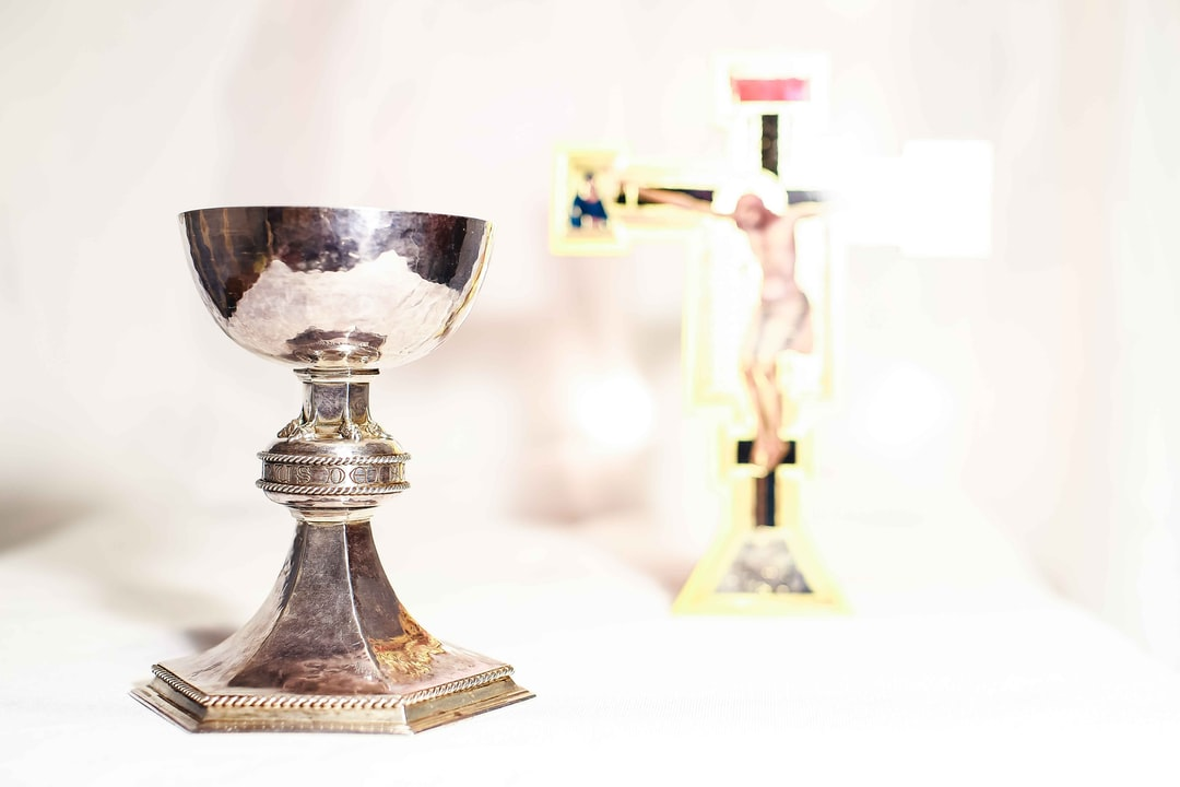 A communion cup with a cross in the background on white