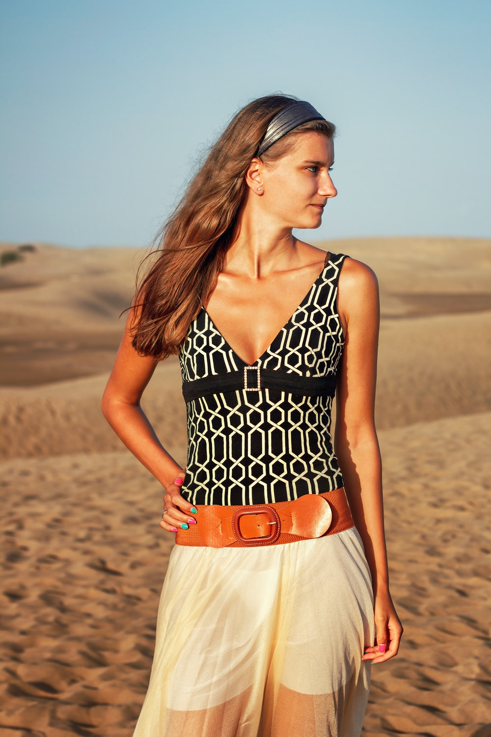 woman in black and white polka dot halter top dress standing on brown sand during daytime