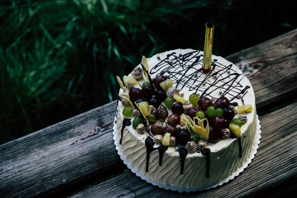 white and brown cake with fruit on top