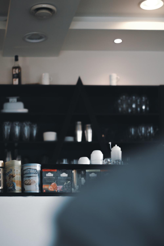 white and blue labeled bottle on black wooden shelf