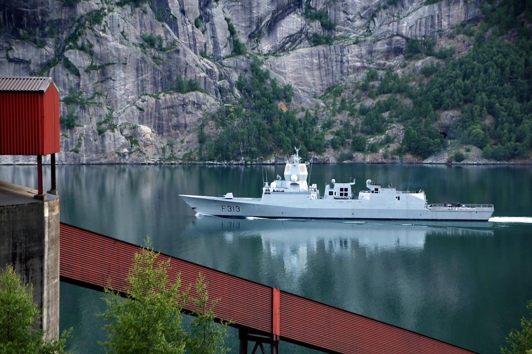 Norwegian frigate HNoMS Helge Ingstad F313 in Sørfjord (June 2018). This ship sunk 5 months later after a collision with an oil tanker. Parts of a mining company on the left side and at the bottom of the photo.  A symbol of military power and its transience.