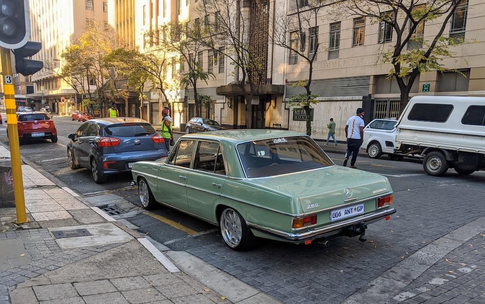 green sedan parked on sidewalk during daytime