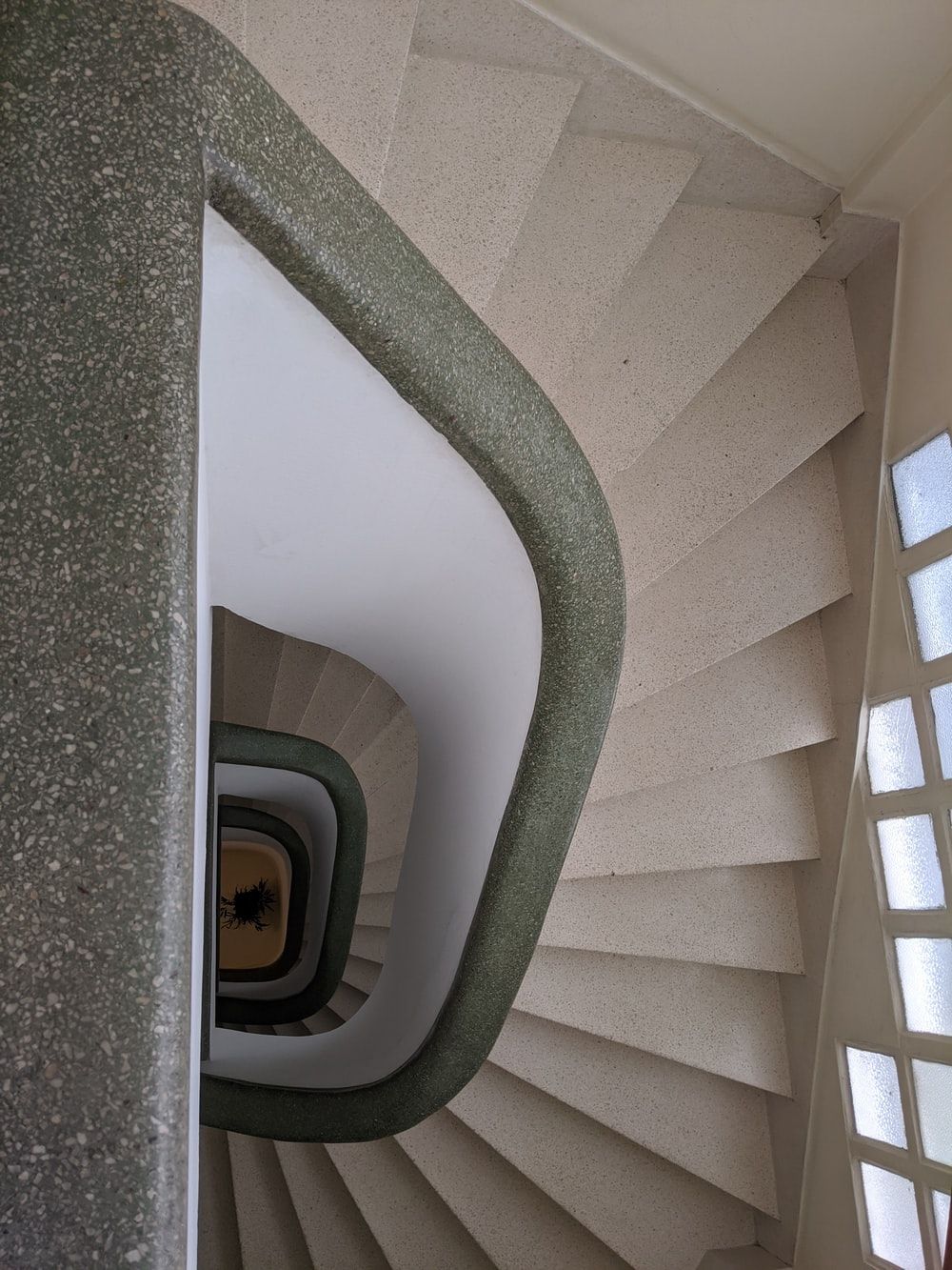 green spiral staircase with white wooden railings