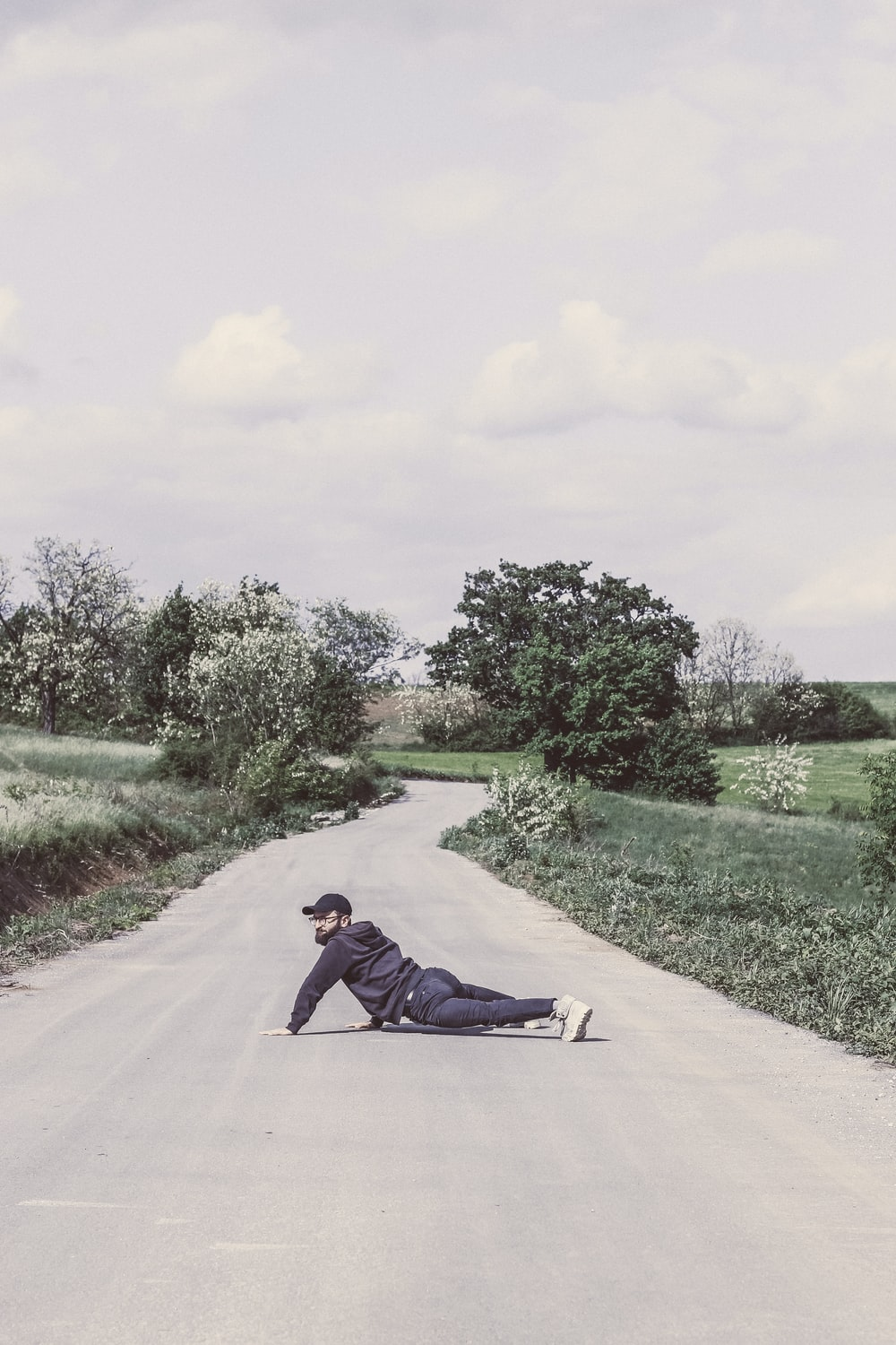 man in black jacket lying on gray concrete road during daytime