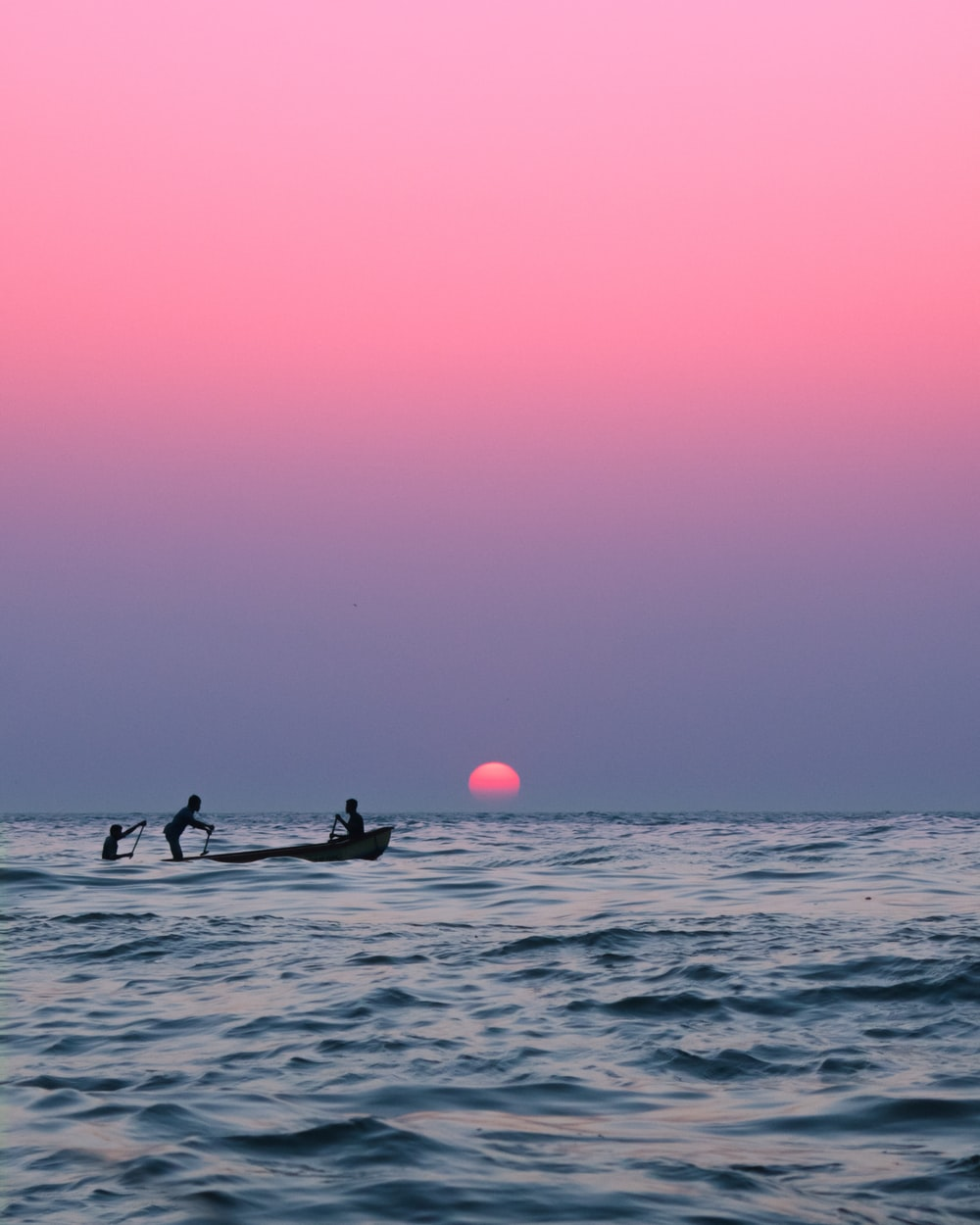 2 people riding on boat during sunset