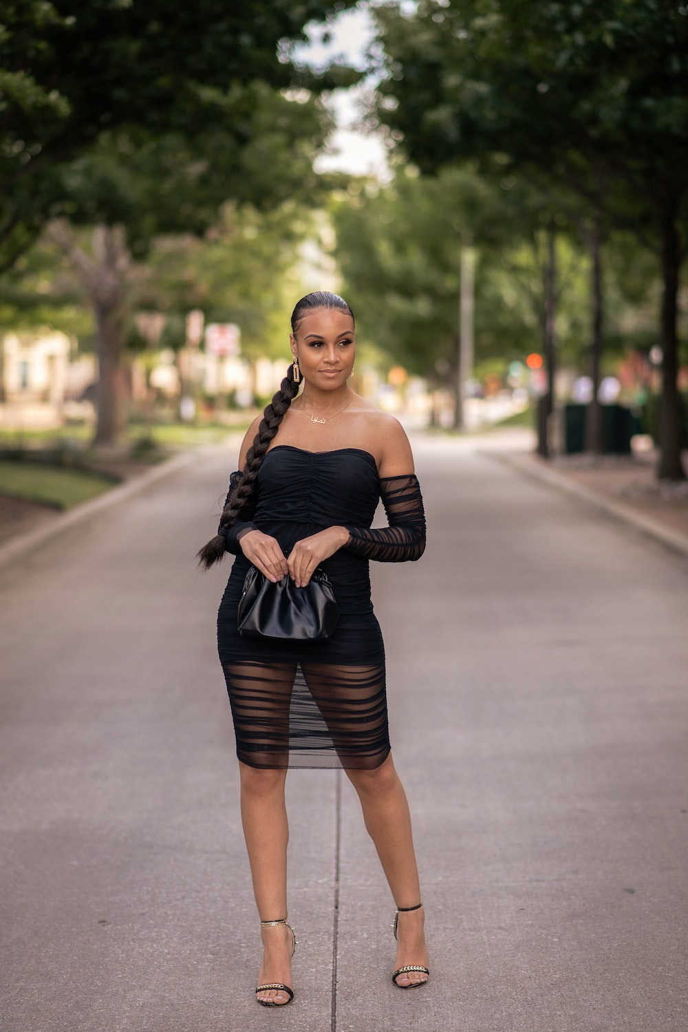woman in black tank top and black skirt standing on road during daytime