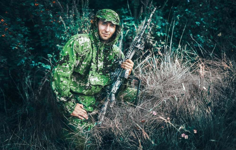 woman in green and black camouflage jacket holding black rifle