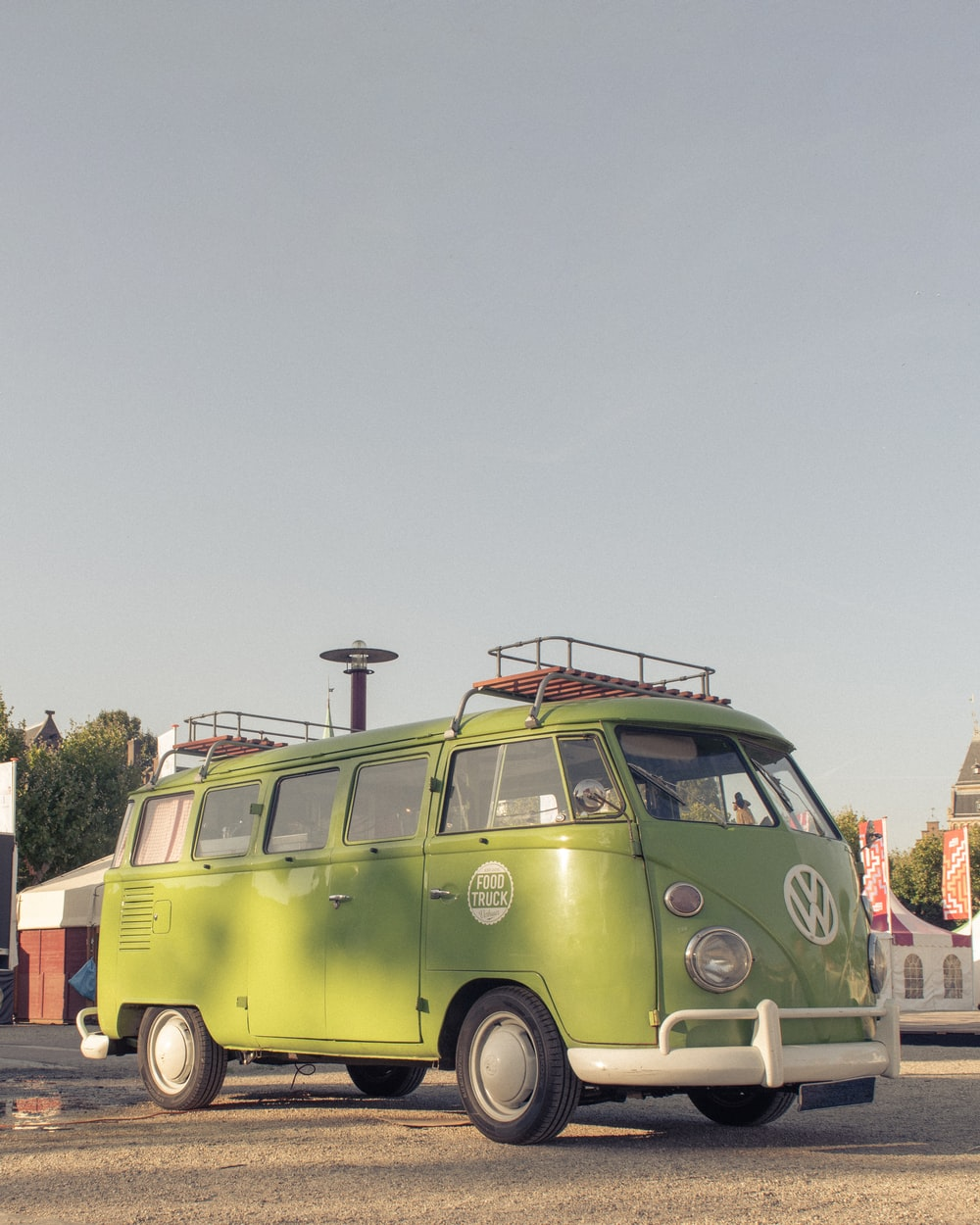 green volkswagen t-2 van parked on gray concrete road during daytime