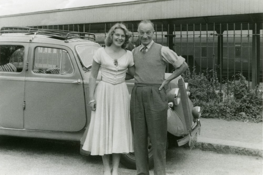 grayscale photo of 2 women standing beside car