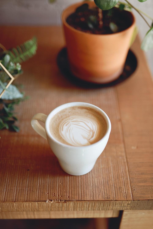 white ceramic mug with brown liquid