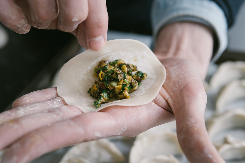 person holding white ceramic plate with green vegetable dish