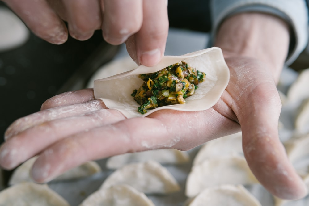 person holding white ceramic plate with food