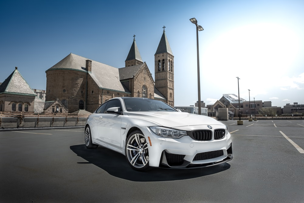 white bmw coupe parked on roadside during daytime