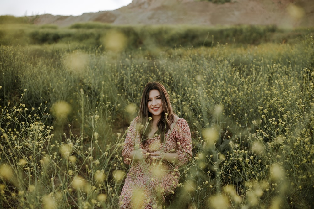 woman in blue and pink floral dress standing on green grass field during daytime