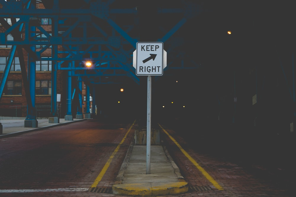 black and white street sign during night time