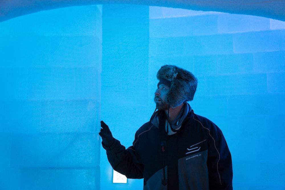 man in black jacket standing near blue wall