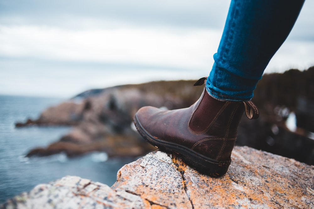 person in blue denim jeans and brown leather shoes standing on rocky shore during daytime