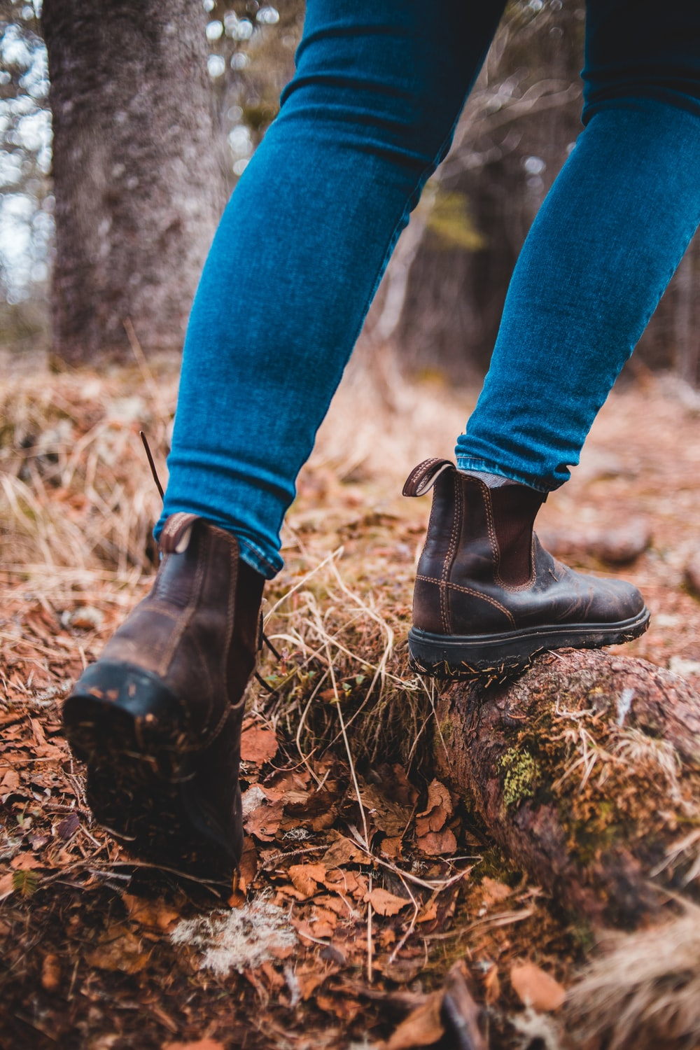 person in blue denim jeans and black leather boots standing on brown dried leaves