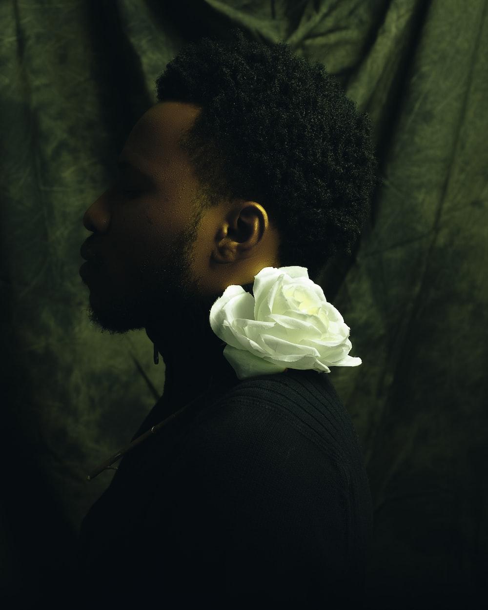 man in black shirt holding white rose