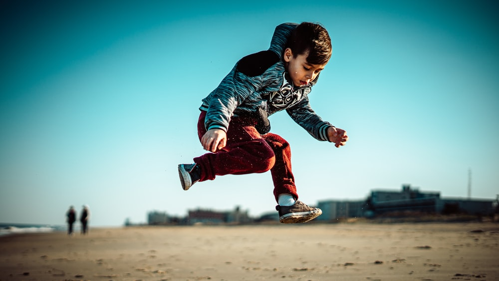boy in blue jacket and red pants jumping on brown field during daytime