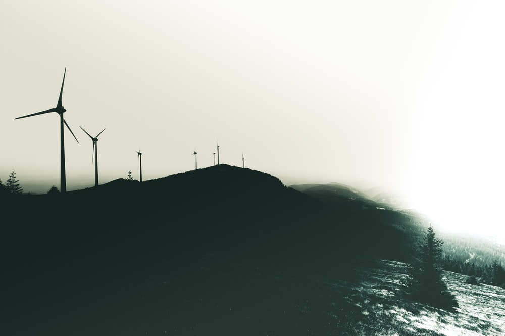 silhouette of wind turbines on hill during daytime
