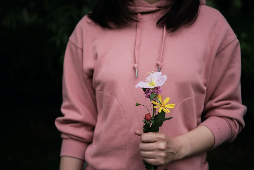 woman in pink hoodie holding white and yellow flower