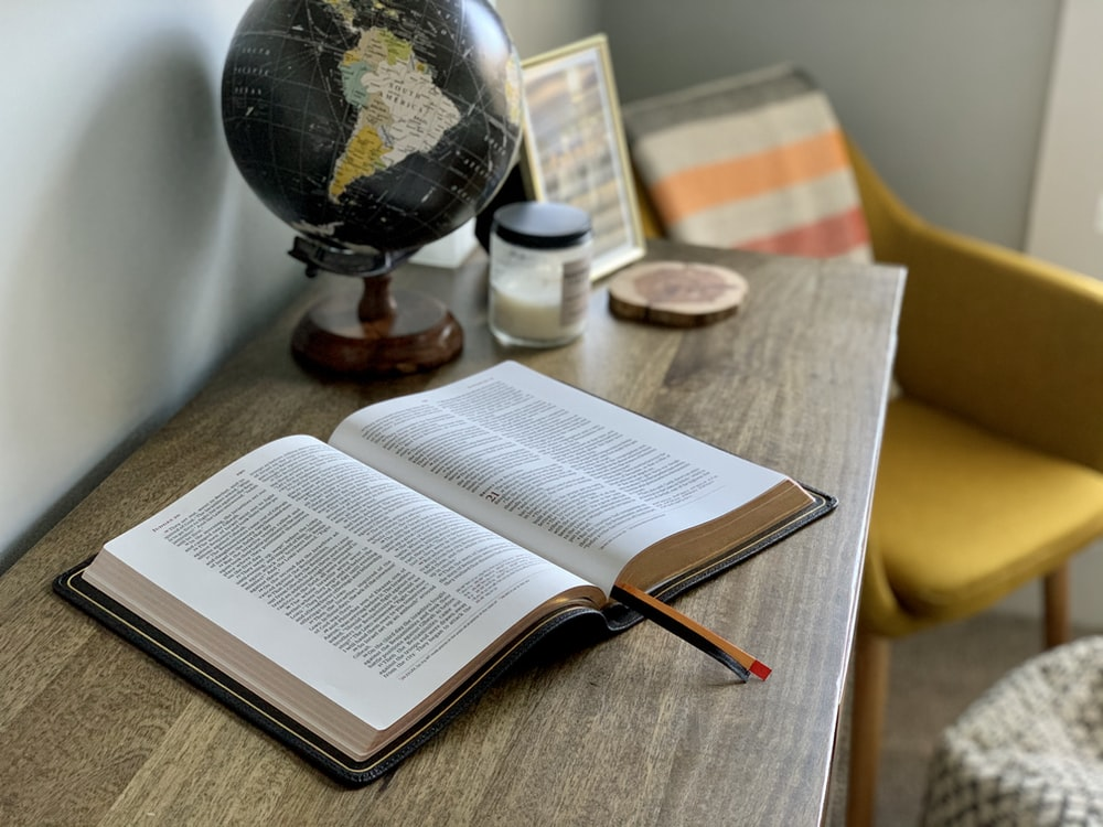 opened book on brown wooden table