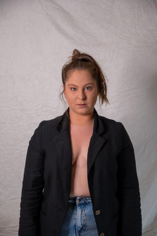 woman in black blazer standing beside white wall