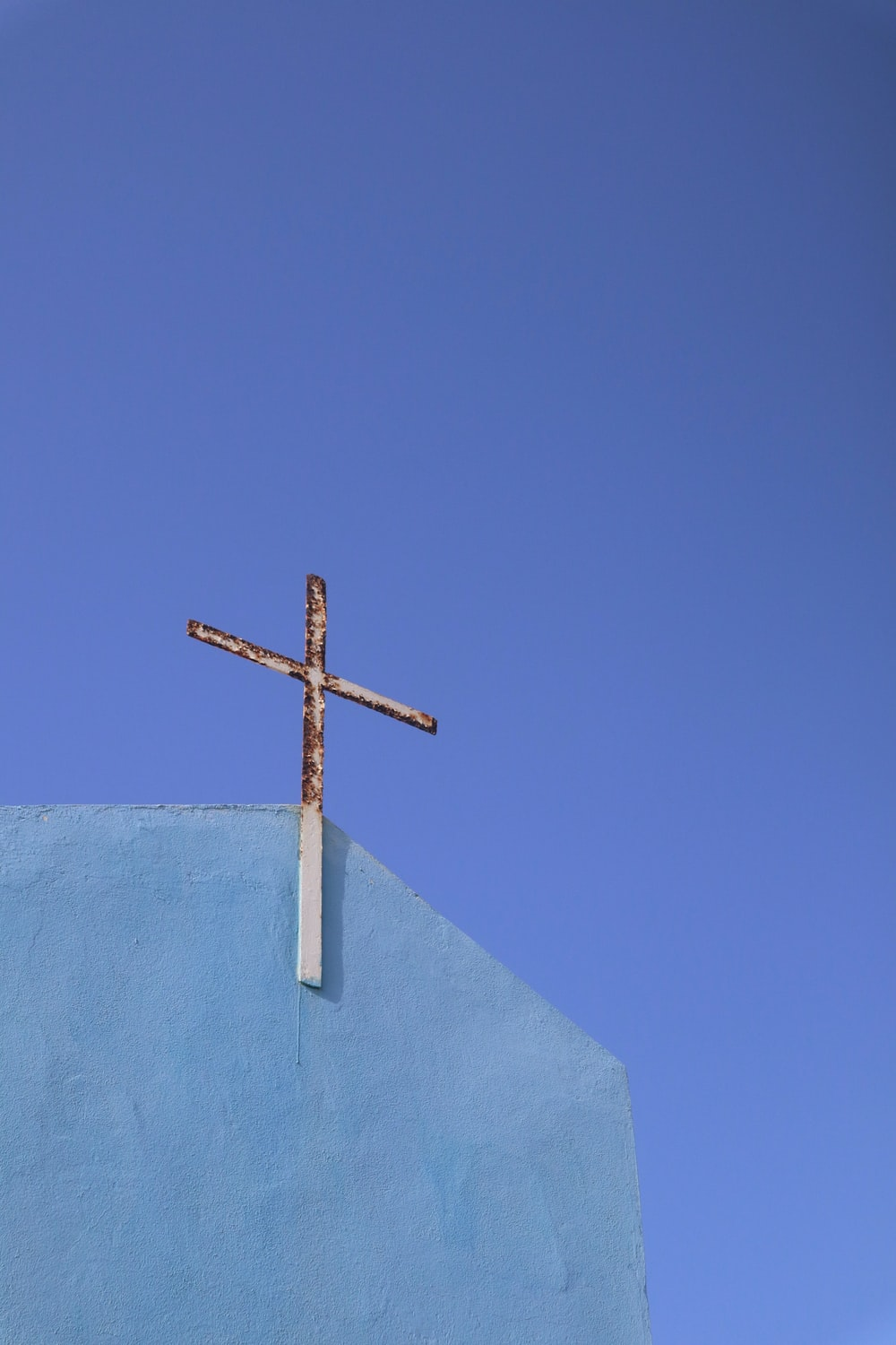brown wooden cross on white textile under blue sky during daytime
