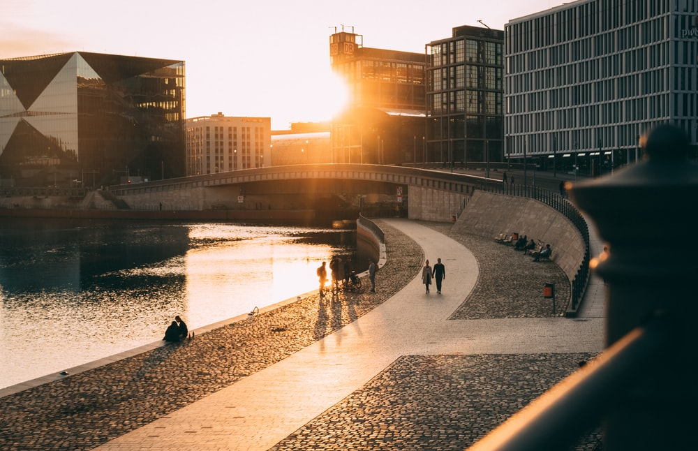 people walking on concrete pathway near body of water during sunset