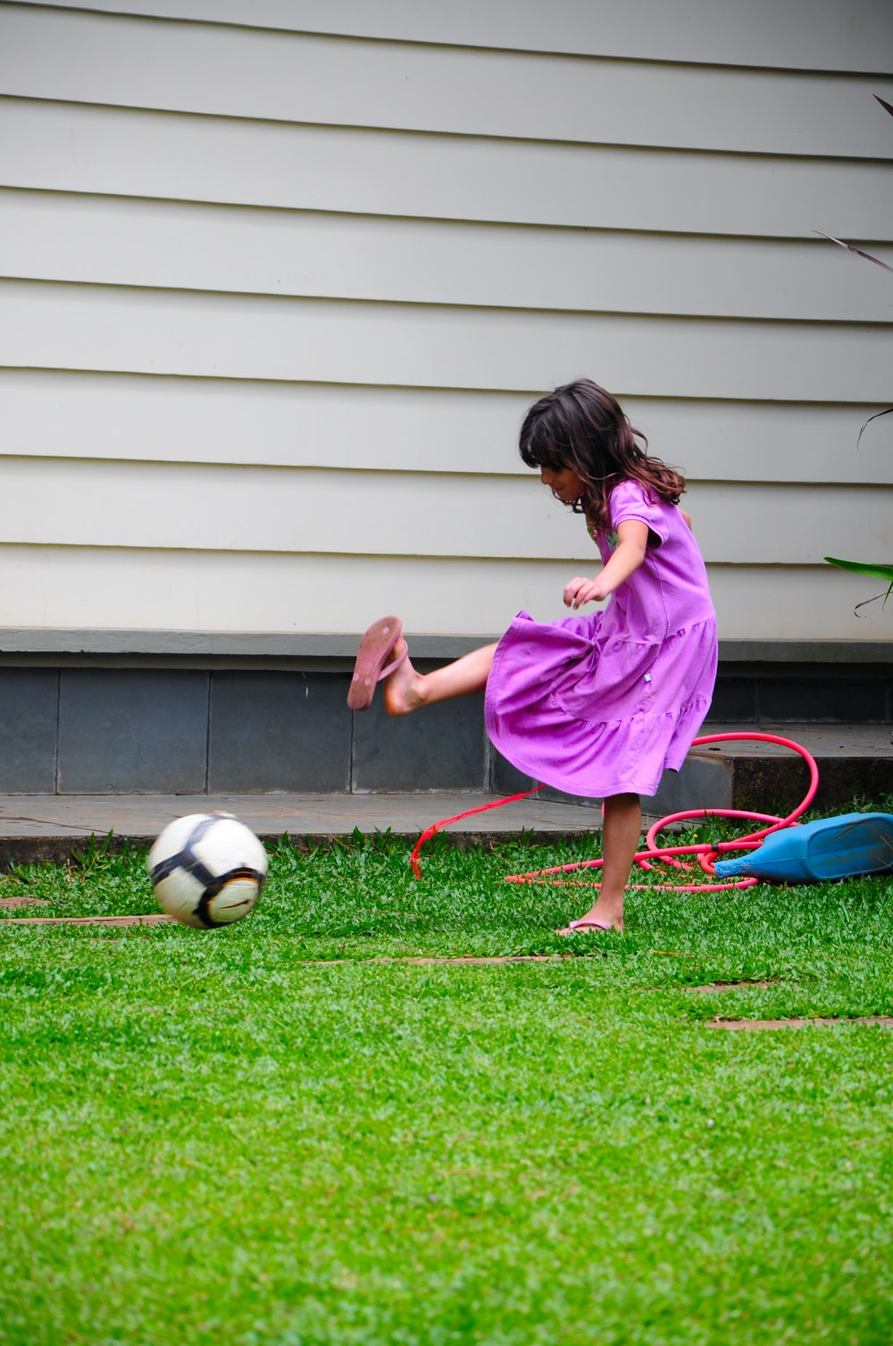 girl in pink dress playing soccer